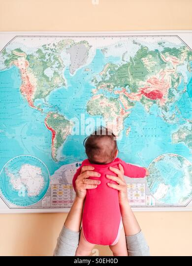 Hello World! Father holding his baby girl up opposite map of the world - Stock Image