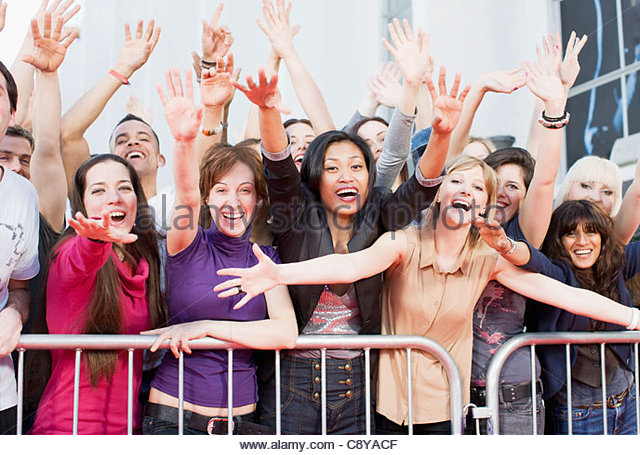 Fans reaching out from behind barrier - Stock Image