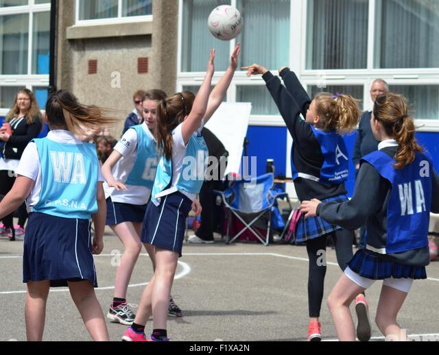 Girls play netball outside - Stock Image