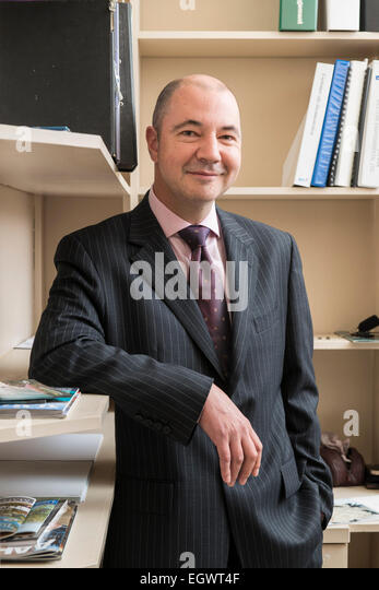 a professional businessman manager in his business suit stands in his small office of an english country house hotel - Stock Image