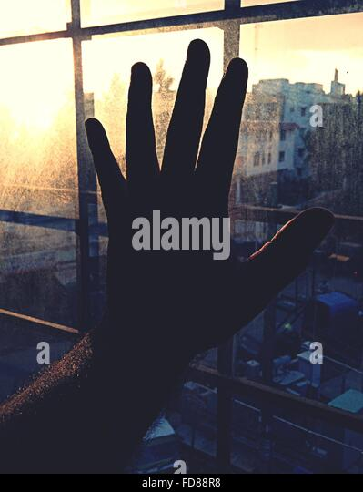 Close-Up Of Silhouette Hand On Window Against Cityscape - Stock-Bilder