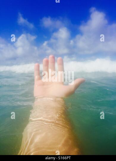 A hand coming out of the water. Maui Hawaii USA. - Stock Image