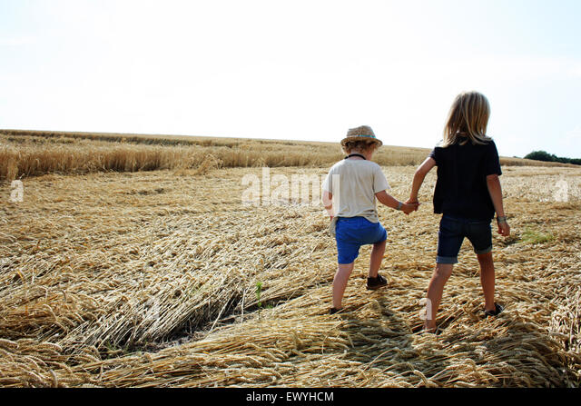 Rear view of two boys holding hands taking a walk - Stock Image
