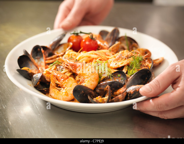 Chef serving bowl of prawns and mussels - Stock Image
