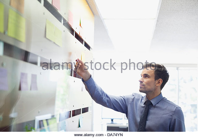 Businessman putting sticky note on wall - Stock Image