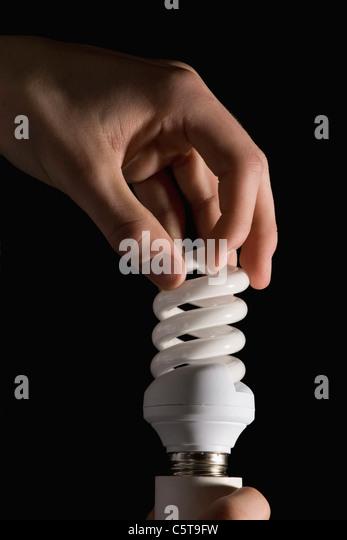 Hand holding energy-saving lamp - Stock Image
