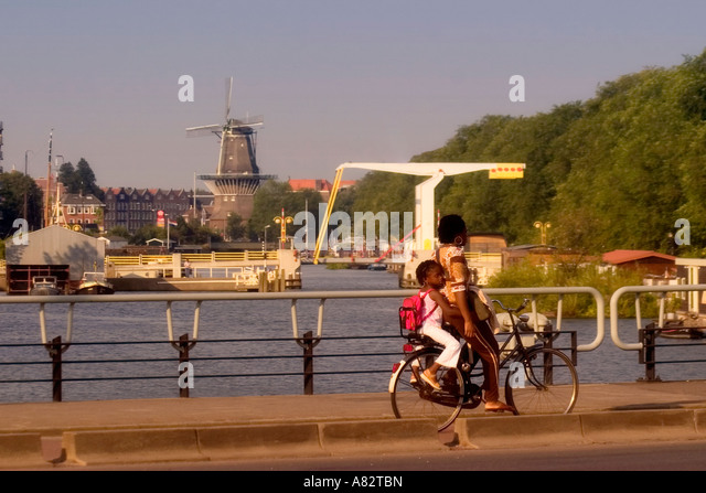 Amsterdam black woman and child on a bicycle backgound draw bridge and windmill - Stock Image