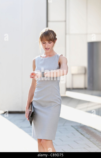 Germany, Bavaria, Munich, Young businesswoman holding purse and checking time - Stock Image