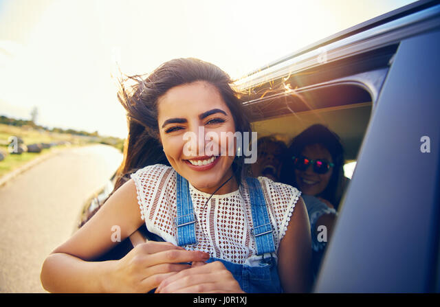 Attractive young woman with a beaming smile leaning out of a car window as she goes travelling on summer vacation - Stock Image