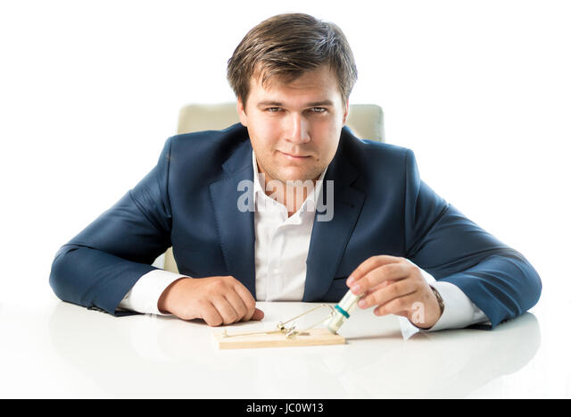 Portrait of cunning businessman putting money in trap as lure - Stock Image
