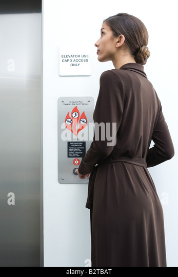 Young professional female waiting for elevator, looking up - Stock-Bilder