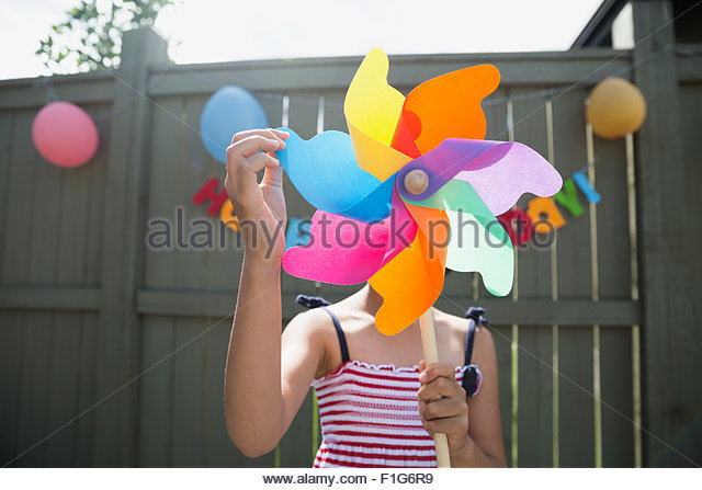 Close up girl holding multicolor pinwheel birthday party - Stock Image