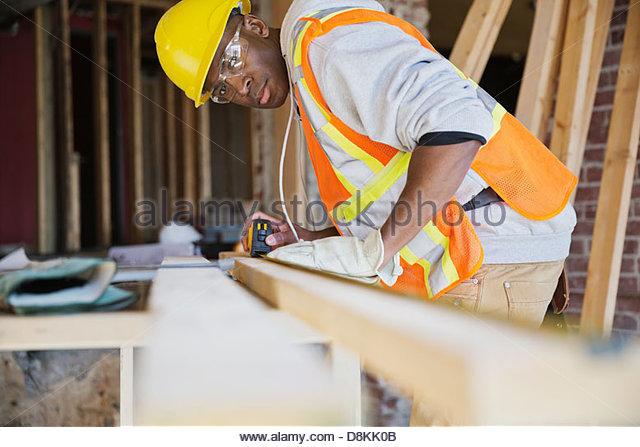 Tradesman measuring lumber at construction site - Stock-Bilder