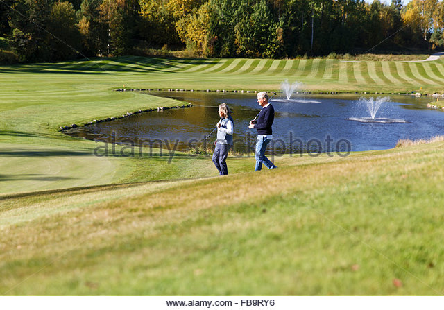 Sweden, Sodermanland, Senior man and mature woman walking through golf course - Stock Image