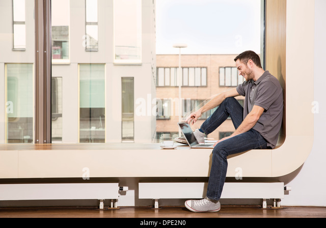 Businessman sitting on windowsill using laptop - Stock-Bilder