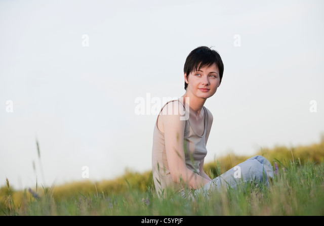 Russia, Voronezh, woman sitting in meadow - Stock Image