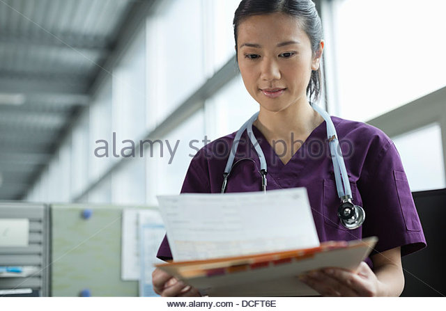 Medical professional reviewing requisition form - Stock Image