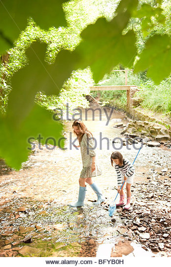 Mother and daughter with nets in stream - Stock Image