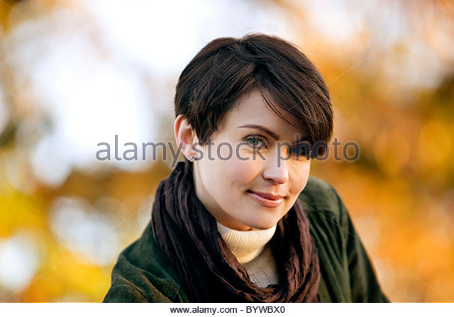 Portrait of a young woman smiling, outdoors - Stock Image