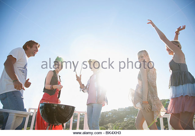 Friends dancing and barbecuing - Stock Image