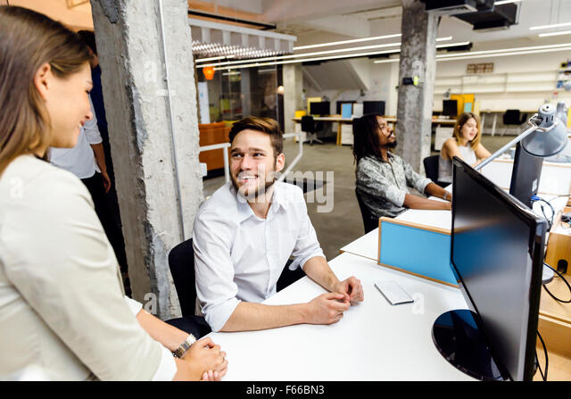 Business colleagues talking in the office  and smiling - Stock-Bilder