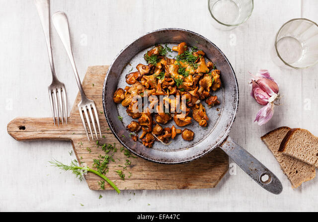 Roasted wild mushrooms in pan on white textured background - Stock Image