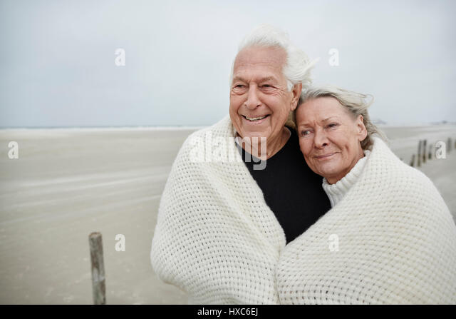 Smiling affectionate senior couple wrapped in a blanket on beach - Stock Image