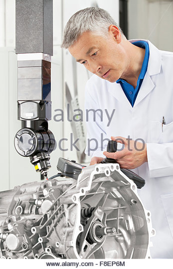Engineer with joystick controlling probe scanning engine block - Stock Image