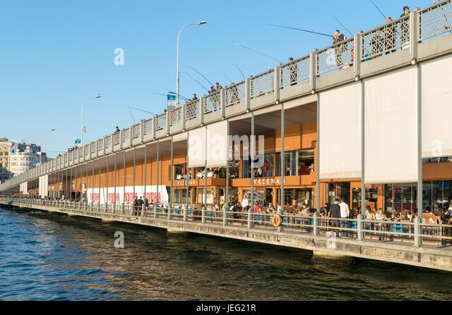 Istanbul, Turkey - April 25, 2017: Galata Bridge with traditional fish restaurants and fishermen fishing - Stock Image