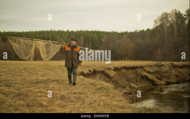 Mature man walking along riverbank carrying traditional fishing net - Stock Image