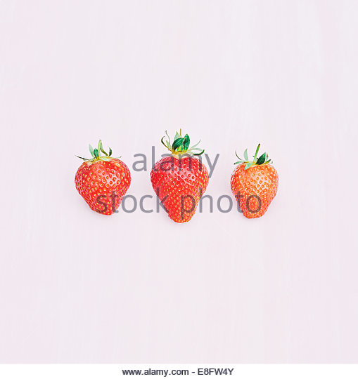 Three strawberries on pink background - Stock Image