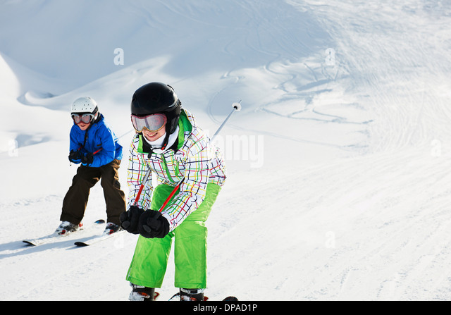 Brother and sister skiing downhill, Les Arcs, Haute-Savoie, France - Stock Image