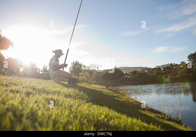 Mature man fishing on peaceful riverbank - Stock Image