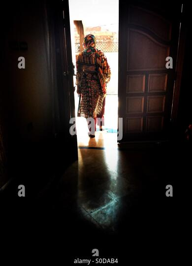 Pakistani woman walking out the house - Stock Image