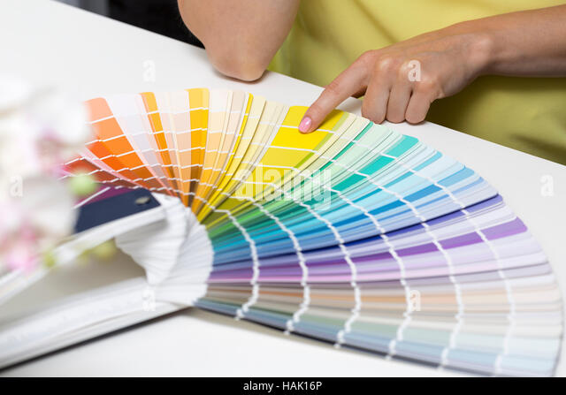woman choosing paint color from tone samples - Stock Image