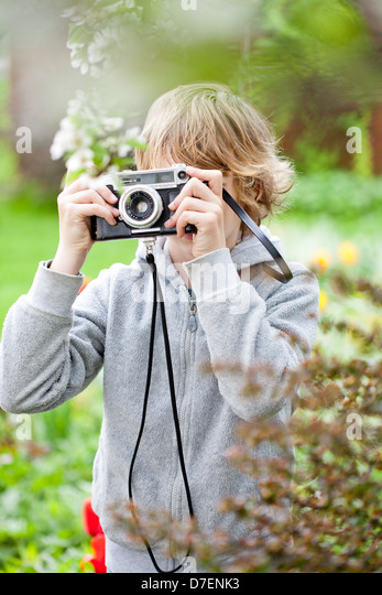 Boy photographing in the garden. - Stock Image