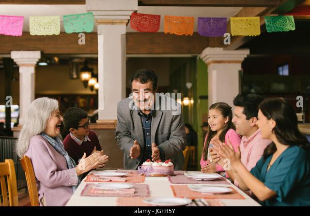 Family celebrating birthday of older man in restaurant - Stock Image