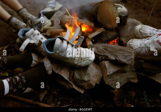 children drying feet around campfire - Stock Image