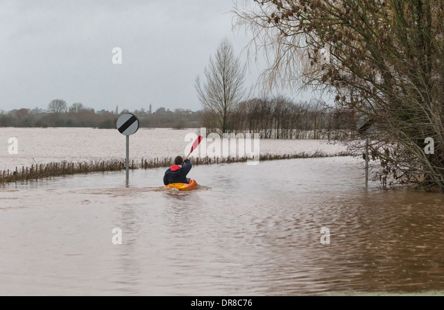 Canoeist paddling down flooded Cuts Rd, Burrowbridge after the River Tone burst its banks in the recent floods - Stock Image