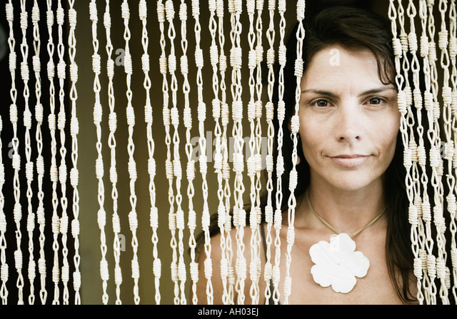 Close-up of a mid adult woman peeking through a beaded curtain - Stock Image