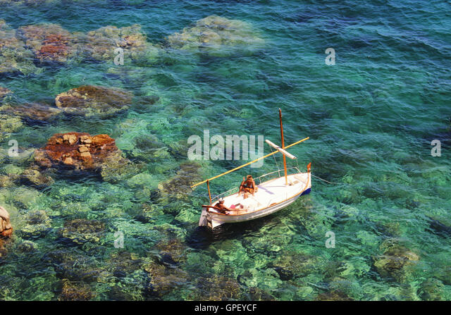 Girona, Spain - August 14, 2016: People taking sun on a boat over the transparent green Mediterranean sea of Costa - Stock-Bilder