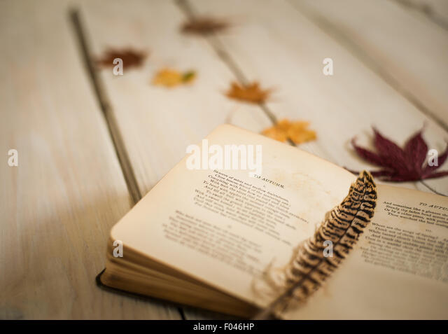 closeup of vintage book of poetry open on ode to Autumn by John Keats, with feather and autumn leaves - Stock Image