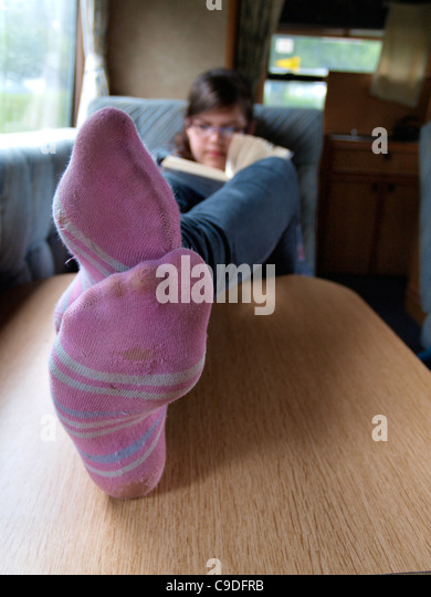 Teen reading a book with feet up on the table, UK - Stock Image