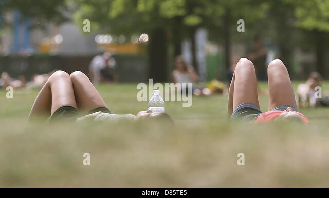 People enjoy the sunshine and temperatures of around 27 degrees centigrade at Lustgarten (pleasure garden) in Berlin, - Stock Image
