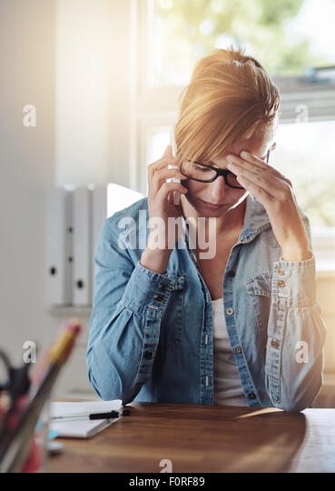 Concerned female entrepreneur talking on a phone as she sits at her desk in her home office with her head resting - Stock-Bilder