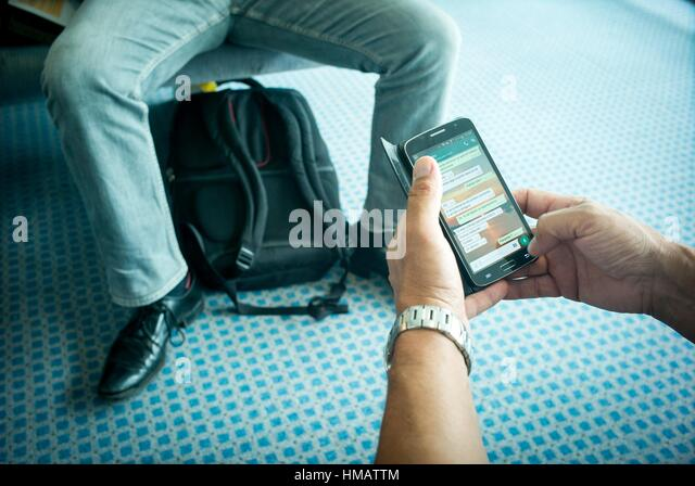 Closeup of the hands of a man handling a mobile phone and in the background a man sitting with a backpack between - Stock Image