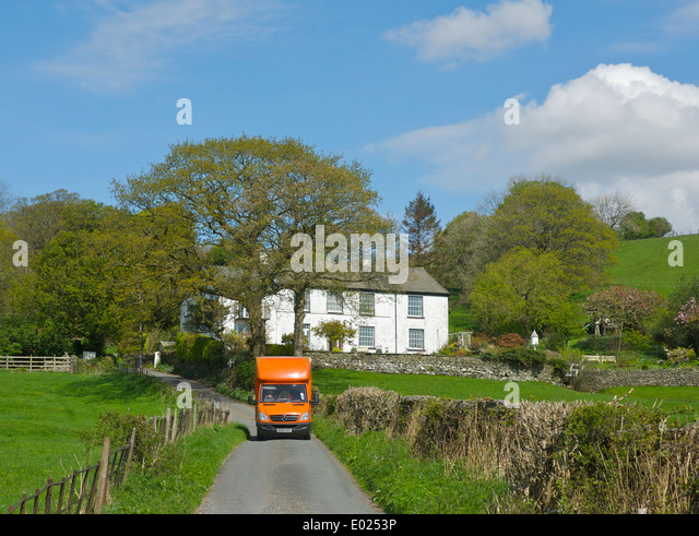 TNT van delivering to a house near Ings, South Lakeland, Lake District National Park, Cumbria, England UK - Stock Image