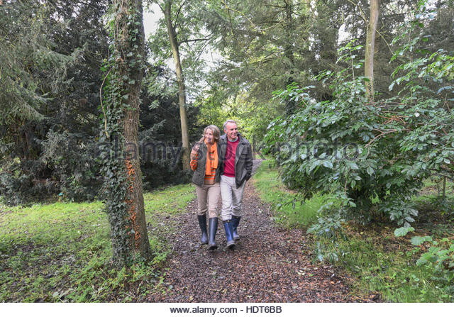 Mature married couple hiking in forest. - Stock Image