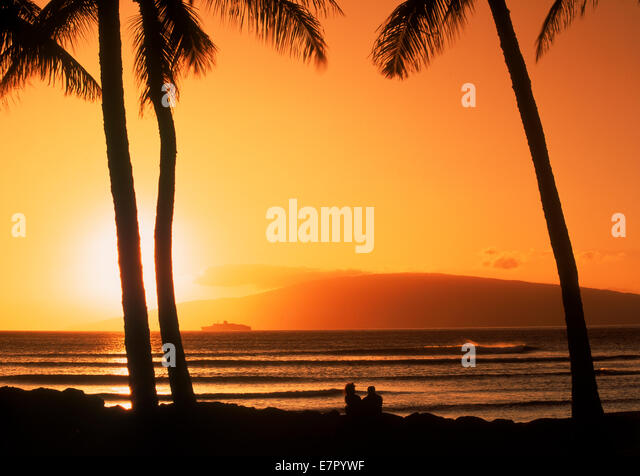 Couple under palm trees on Maui at sunset with island of Lanai on horizon - Stock Image