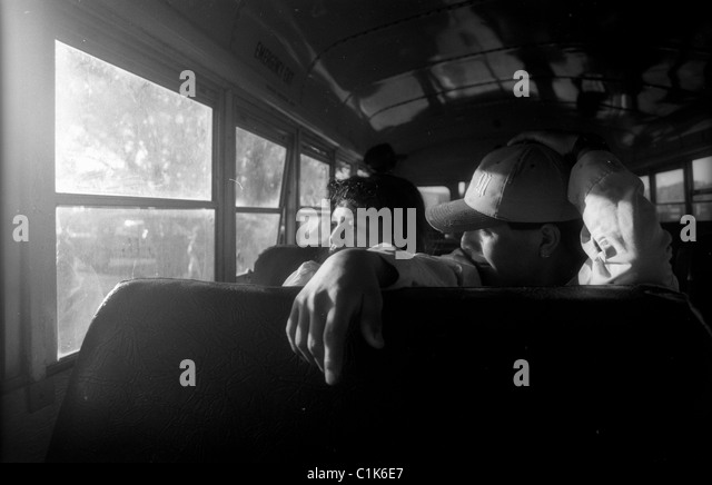 Tired farm workers riding bus - Stock-Bilder